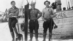 Black and white photograph Three men standing in front of the Josuhée schooner. The person on the left is holding a shovel, the one in the centre is holding a saw and the one on the right is holding an axe.