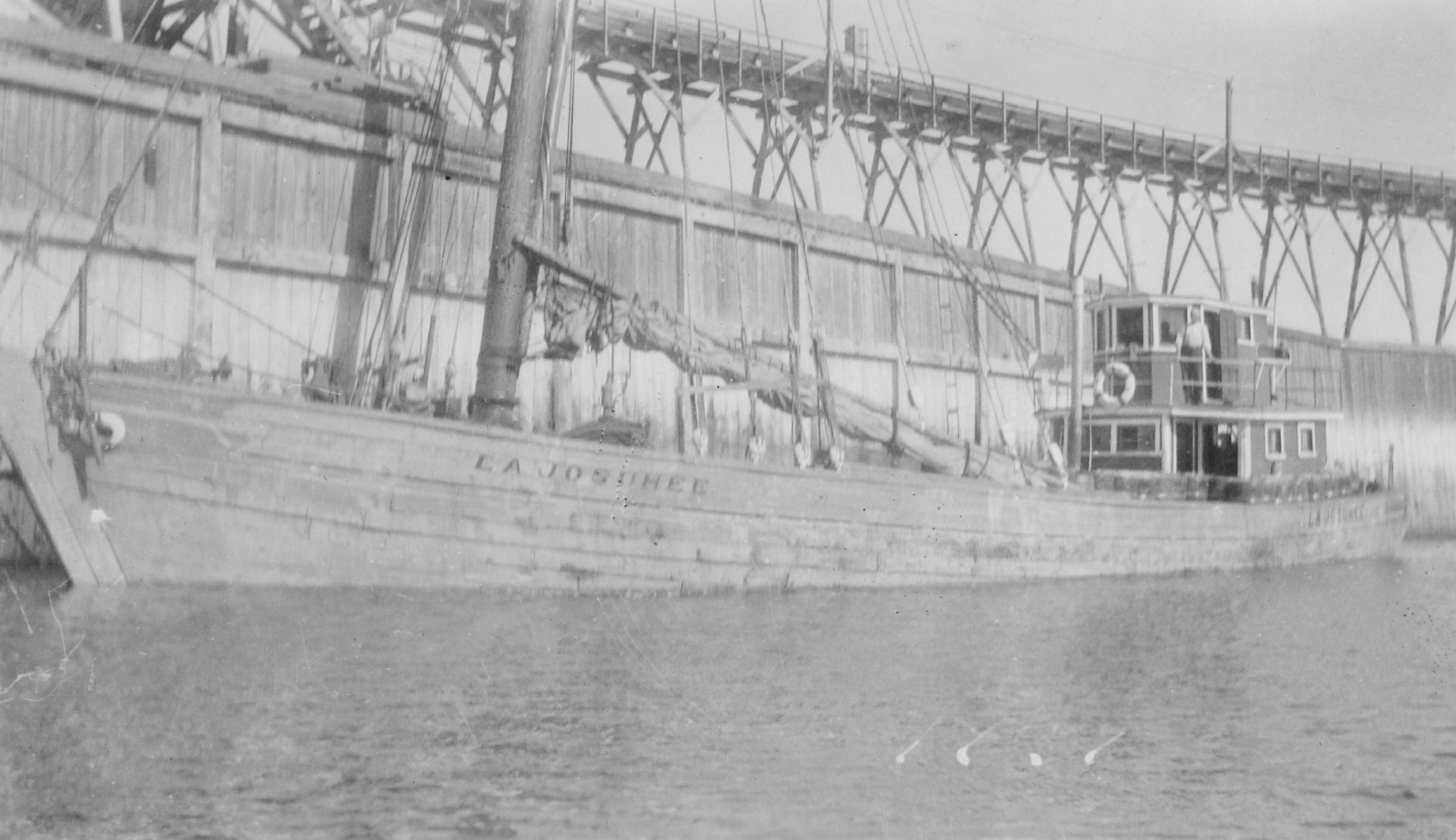 An old black and white photograph of the Josuhée. The wooden ship has its sail lowered, with its name clearly visible. At the back, Captain Joseph Desgagnés is standing proudly outside his cabin. There is a wooden dock in the background.