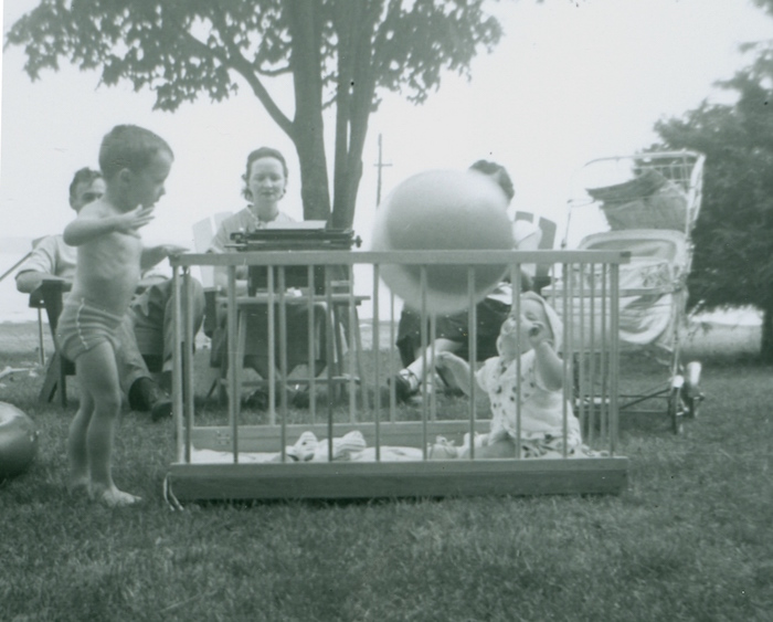 This black and white photograph, taken outdoors, shows a baby in a park playing with a ball in the foreground. Left of the child, a young boy is standing on the grass. Three adults are sitting in the back. The woman in the middle is typing on a typewriter resting on a small table in the grass.