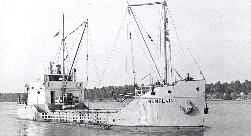 Photographie en noir et blanc. On observe le caboteur Champlain dans toute sa longueur, vue de devant. Le bateau est pâle et son nom est inscrit en lettre noire à la proue. Il a deux mâts de charge et ne semble transporter aucune cargaison. Trois hommes se tiennent au-devant du bateau qui flotte sur l'eau.