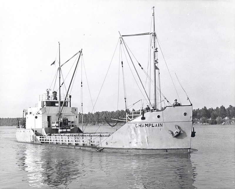 Black and white photograph. This picture gives us a front view of the Champlain coaster in all its length. The ship is light-coloured, with its name written in black lettering on its prow. It is also fitted with two boom masts but does not seem to be carrying any cargo. Three men are standing at the front of the ship, which is floating on the water.