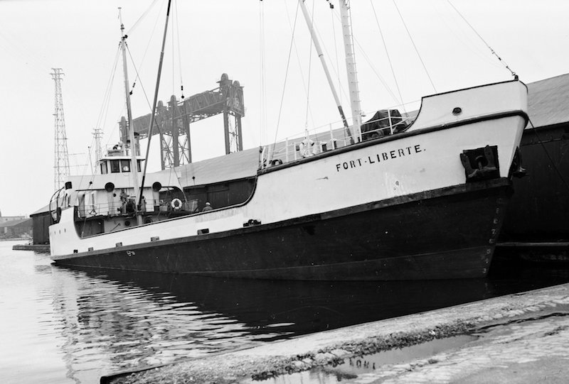 Black and white photograph. This picture gives us a front view of the Fort Liberté coaster in all its length. The ship's hull is painted black and white, with its name written in black lettering on its prow. It is also fitted with two boom masts but does not seem to be carrying any cargo. Part of a lock canal is visible in the background.