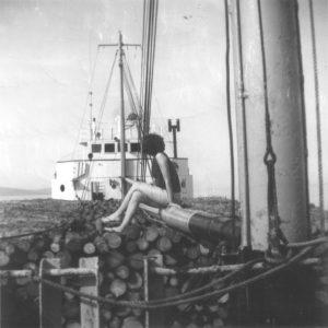 Photographie en noir et blanc prise sur le pont du navire, à la poupe. Le navire est rempli de cordes de bois, sur lesquelles est assise une femme de dos. Devant elle, un mât de charge et la cabine blanche du navire.