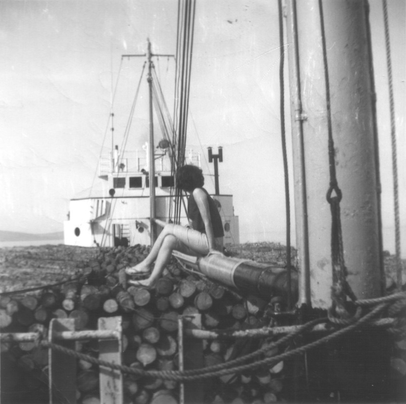 A black and white photograph taken on the deck of the ship, at stern. The ship is filled with rigging, on top of which a woman is seated, facing away. In front of her, the boom mast and white ship's cabin are visible.