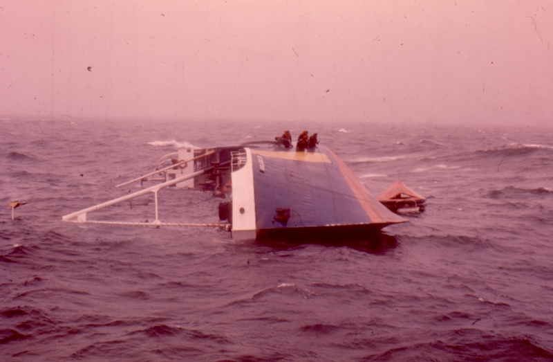 Colour photograph of a half-submerged l'Aigle d'Océan. The photograph was taken in front of the ship's hull. The ship is lying on its side with its masts immersed in water. Crew members are waiting to be rescued on the blue and yellow hull of the ship.