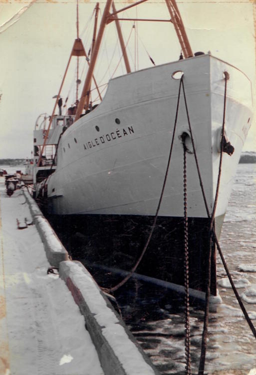A photograph of the ship l'Aigle d'Océan at dock, front view. The ship is white but has a black stripe on the lower portion of its hull. The name of the ship appears on the upper portion of the hull, just under the portholes. There are little clumps of ice in the water.