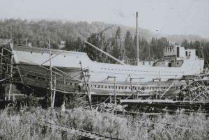 Cette photographie en noir et blanc montre une goélette en construction. Le bateau semble presque achevé. Des échafaudages de bois se dressent de part et d'autre de la charpente. Quelques hommes - très petits sur la photo - s'affairent sur le bateau. Devant le bateau, un homme se tient dans les herbes hautes et observe la scène.