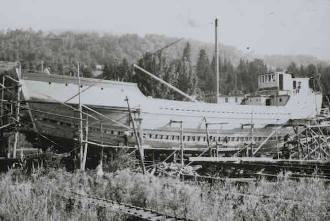 This black and white photograph shows a schooner under construction. The ship appears to be almost finished. There is wooden scaffolding all around the structure. A few men—tiny in the photograph—are busy working on the ship. In front of the ship, a man is standing in the tall grass observing the scene.
