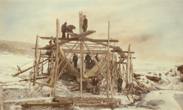 View of a schooner under construction. The structure of the ship is surrounded by scaffolding. There are men in work clothes standing on the hold of the ship and the scaffolding. A woman, a child and another man are standing in the foreground. This photograph was taken in winter. The photo has been coloured to give it a sepia tone.