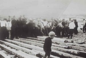 An old black and white photograph. In the foreground, a young child walks alone on wooden planks. In the background, around two dozen men are pushing a schooner towards the river.