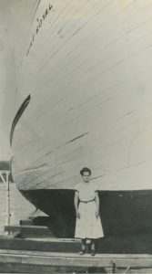 A black and white photograph. A woman wearing a light-coloured dress is standing in front of a wooden ship. The woman looks tiny next to the massive ship. In the upper left corner of the photograph, we can see the name of the ship painted on the hull: Mont Royal.
