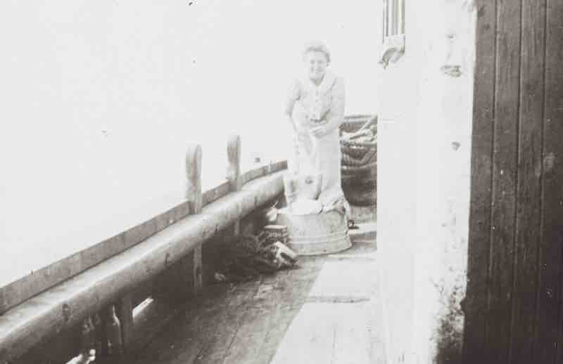 A black and white photograph. A young smiling woman, hair tied back, is standing on the deck of a ship. She appears to be washing dishes in steel pails. There are a few bundles of rigging all around her.