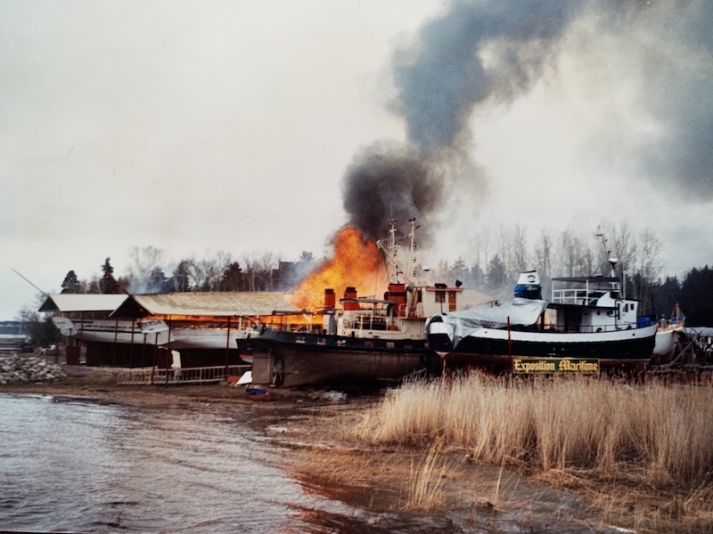 """View of a riverbank with four ships. In the middle, flames and grey smoke rise out of a wooden ship. In the foreground a sign in the brown grass reads: """"Exposition maritime""""."""