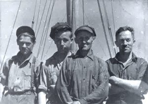 A black and white photo of four men in work clothes. On the left, two teenagers, in the middle, an older man, and on the right a man in his prime. Behind them we can see two masts and some rigging.