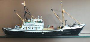 Maquette de la goélette Havre-Aubert. Le petit bateau est en bois. Sa portion inférieure est noire et la portion supérieure est blanche. Des petites chaloupes de sauvetage et du matériel de construction miniature garnissent le bateau. À la proue, on peut lire le nom de la goélette.