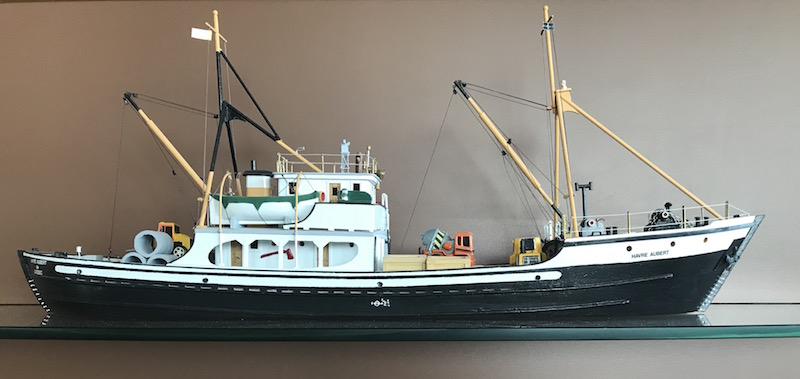 Model of the Havre-Aubert schooner. A small wooden model of a ship. The lower portion is black with the upper portion painted white. Small lifeboats and miniature construction materials complete this model ship. The name of the schooner is written on its bow.