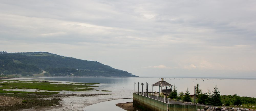View of the bay in Saint-Joseph-de-la-Rive taken from the site of the Musée maritime de Charlevoix. A wooden dock in the foreground juts into the river.