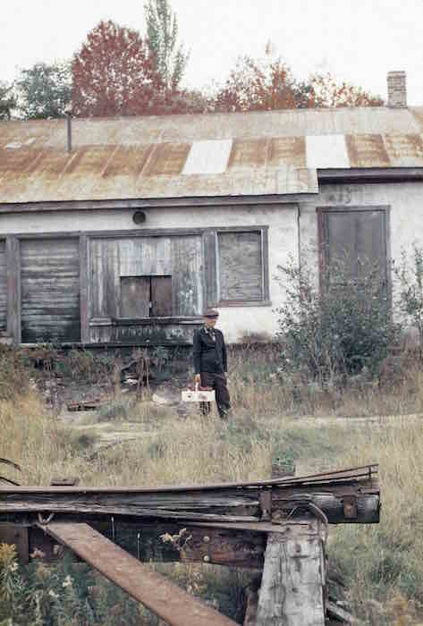 An elderly man is standing in the centre of the frame. He is carrying a bushel of apples. There are tall grass and a structure made of rusty metal and wood in the foreground. A boarded-up building is visible in the background.