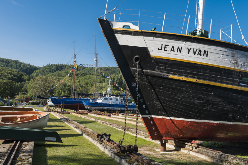 A photograph of the site of the Musée maritime de Charlevoix. In the foreground we see part of the Jean-Yvan schooner's hull, painted white, black, yellow and red. Rails form straight line leading to two more boats adorned with flags. To the left, a couple of rowboats are resting on the ground.