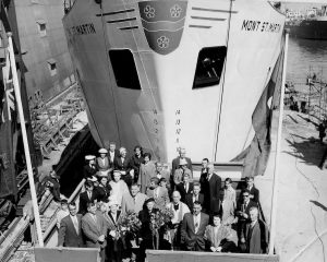 Black and white photograph. In the foreground, a group of people in Sunday clothes on a small stage. In front of them, a priest is standing next to two women holding bouquets of flowers. Behind them, towering over the group, is the huge white hull of a ship. The name of the ship is painted on both sides of the hull: Mont St-Martin.