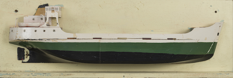 This colour photograph shows a model of the Mont St-Martin coaster. The model is a cross-section. The hull features a black and a green stripe. The upper portion and cabins are painted white. The ship's propeller is visible in the back.