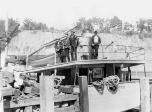 A black and white photograph with, to the left, a dock with lumber strewn about, and to the right, the Mont St-Joseph schooner. The name of the ship is partially hidden by the rigging. Four people are posing on the ship: three young men and their parents.