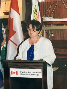 A woman is standing behind a lectern featuring the logo of Heritage Canada. She is giving a speech. Behind her there are two flags and a scale model of a ship.
