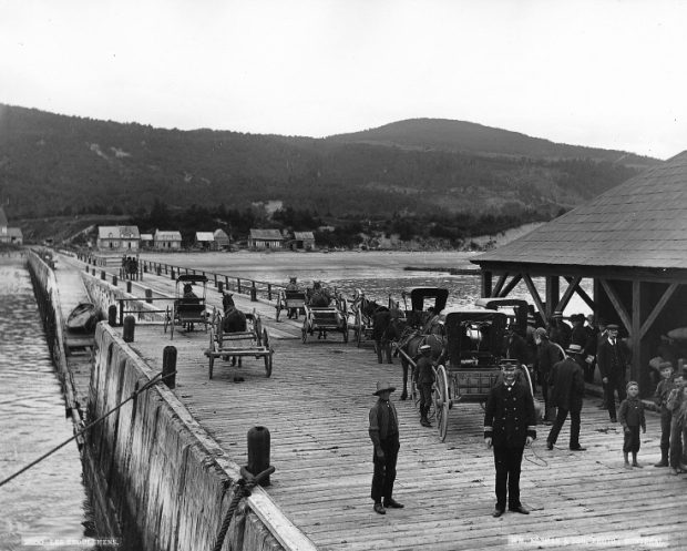View of the dock at Les Éboulements (Saint-Joseph-de-la-Rive), circa 1890. This photo was taken from a ship moored at the end of the dock, the shore, along with a few houses are visible on the horizon. The wooden dock. In the foreground, a man stands in uniform. Next to him are a few children and other men. Some horse-drawn carriage in the background.