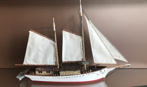 Model of the Rose-Alba sail-powered schooner. The hold of the ship is white, with a small red stripe at the bottom. The ship is fitted with miniature ropes and a small lifeboat at its stern. The model sports four white sails.
