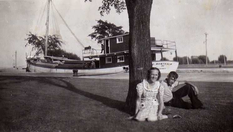 A black and white photograph. In the foreground, a young man and woman are sitting on the grass near a tree. Behind them there is a wooden ship, on which three people are barely discernible. The boat seems to float on a narrow canal.