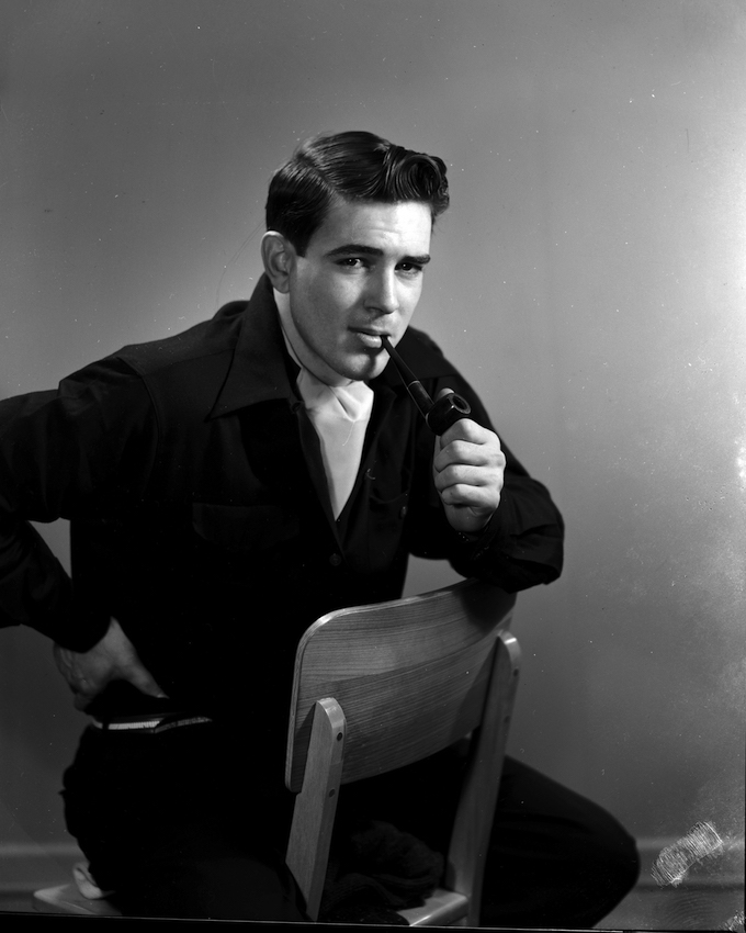 A black and white portrait of a young man He is sitting backwards on a wooden chair, with the backrest against his belly. The young man is wearing black, with a white scarf knotted around his neck and a pipe in his mouth.