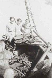 A black and white photograph of three young women holding on to a ship's bow. In the foreground are some logs, rigging and an anchor.