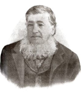 A black and white portrait of a man. The picture is cut at the bust line. On it we see an aged man with short hair sporting a white beard under his chin. The man is wearing a jacket.