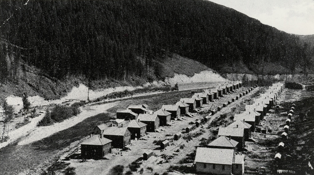 Two long rows of miners cottages beside a river.