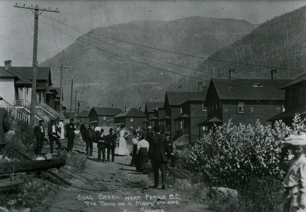Men and women walking along a street. Wood sided houses are on both sides