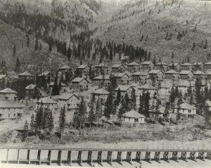 A row of coke ovens in front of rows of one-story cottages and two- story boarding houses.