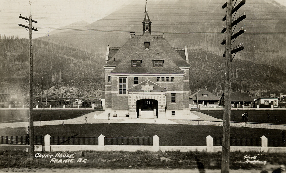 The Fernie Courthouse building surrounded by lawns and an iron fence.