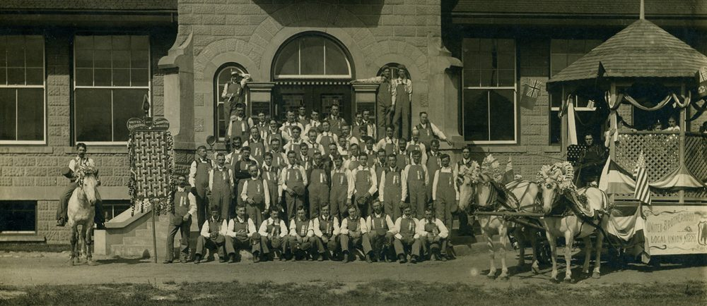 Five rows of men standing or kneeling in front of a building. Man on a horse is on the left, a parade float on the right.