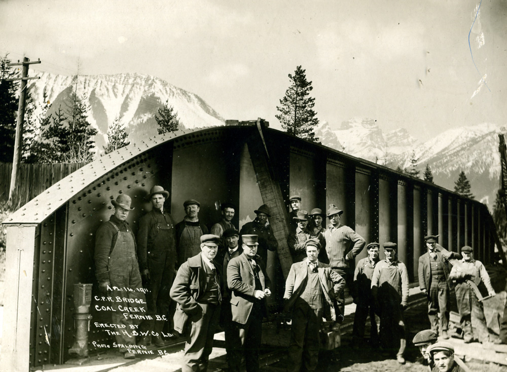 Two rows of men standing in front of a railroad bridge.