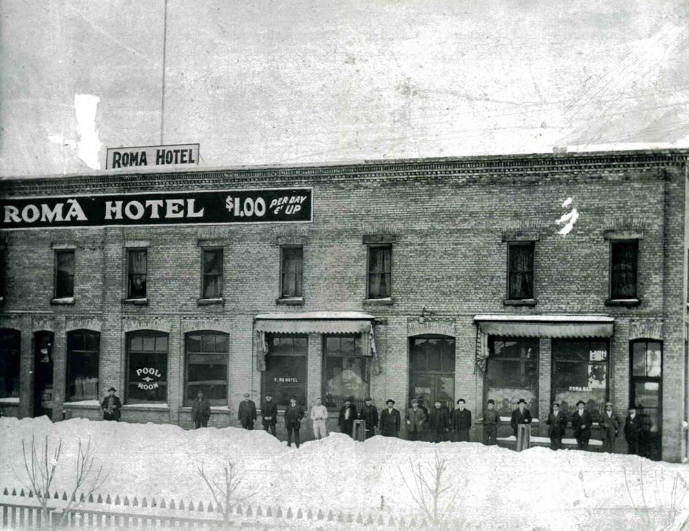 A group of men standing in front of the Roma Hotel in winter.