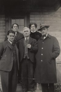Group of three men and two women standing in front of a house.