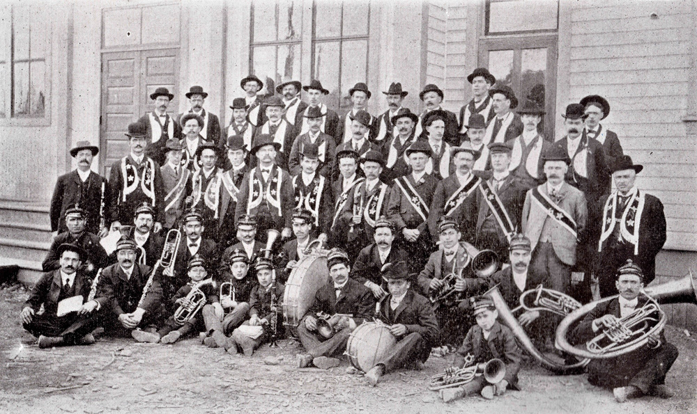 Five rows of men; front two rows of men are holding instruments and are sitting. Three rows of men in regalia stand behind them.