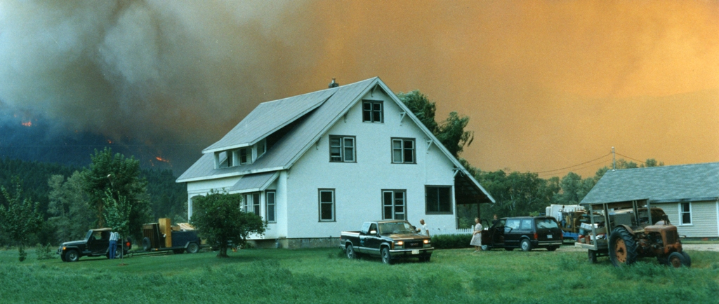 A family evacuates from their home. Fire rages in the background.