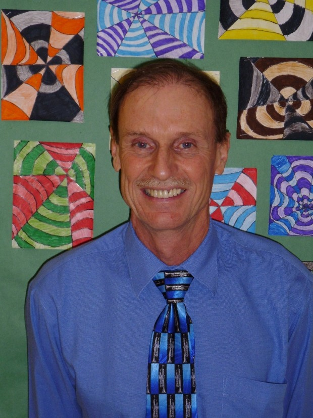 Man in a shirt and tie smiles at camera.