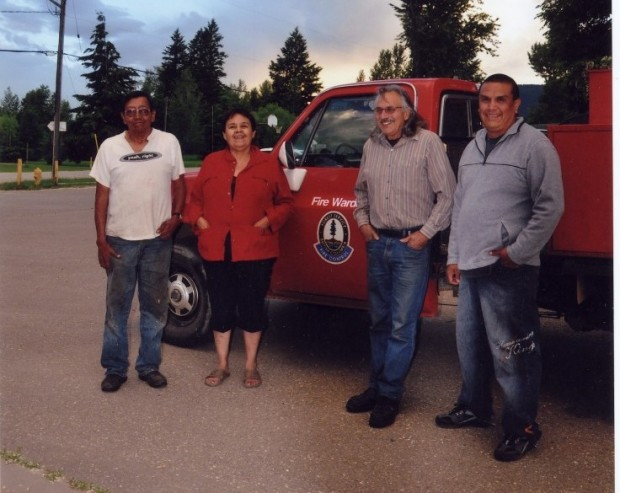 Three men and a woman stand in front of a red truck.