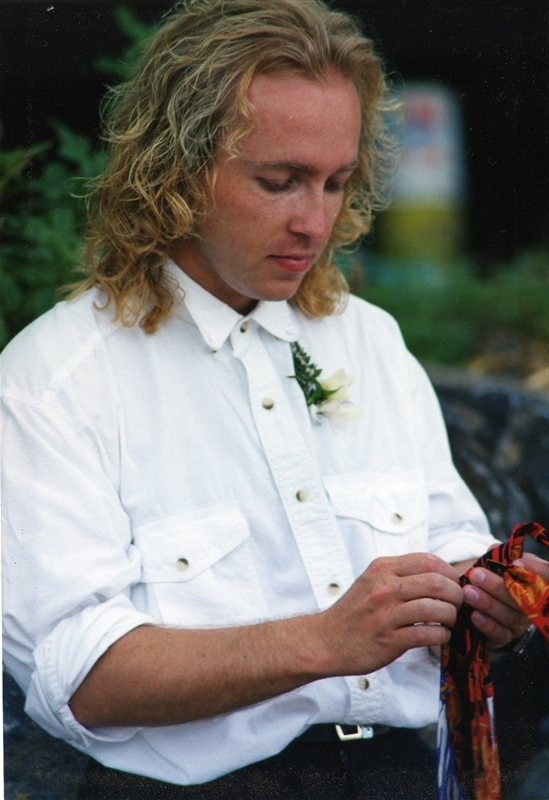 Man in white western style shirt with a white rose corsage. Holds a piece of bright coloured fabric.