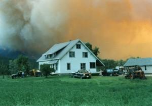 Maison blanche avec des gens près de leur véhicule stationné. Ciel est de couleur jaune-orangé. Incendie sur la colline.