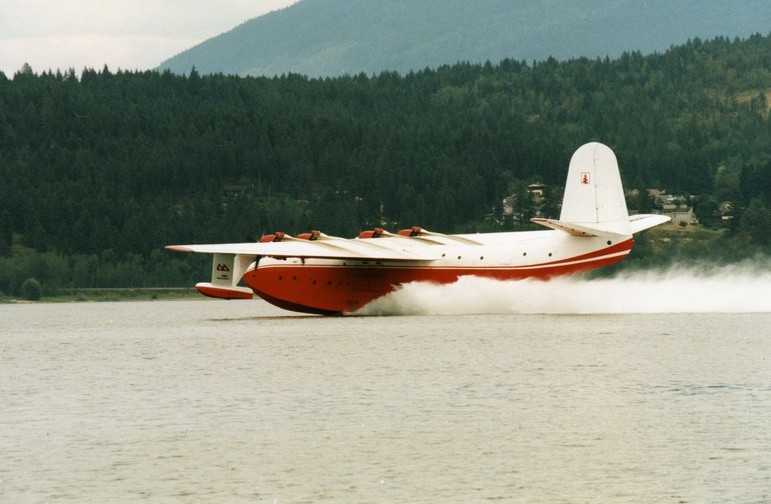 Red and white float plane lands in water. Hillside in background.