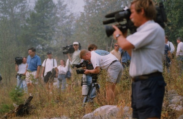 13 reporters in brush, some with large cameras over their shoulders.