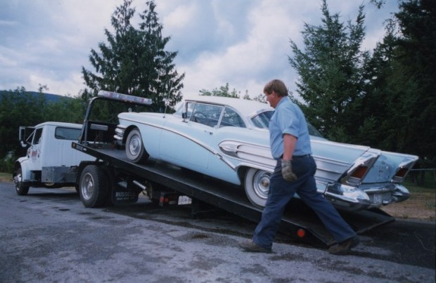 Blue and white collector's car loading on a flatbed hitched to a tow truck. Man walks in front of car.